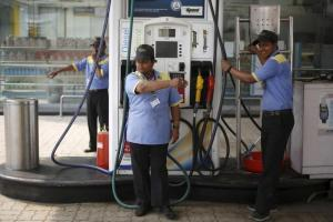 Employees direct a vehicle towards the fuel pump at a fuel station in New Delhi, India, March 7, 2016. Credit: Reuters/Adnan Abidi/Files