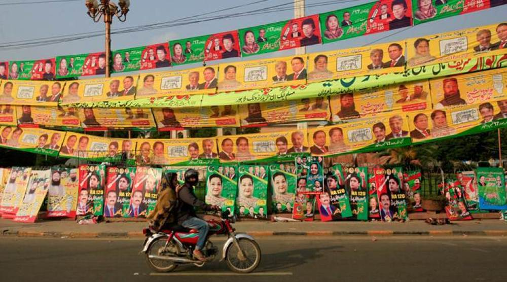 Residents ride on bike past election campaign signs along a road in Lahore