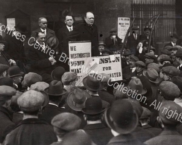Photo shows WSC on a platform addressing a crowd of men wearing caps and hats.
