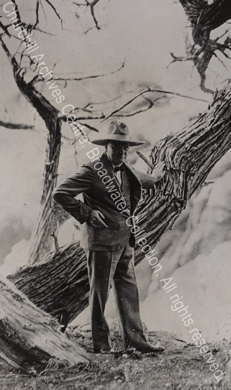 Photo of WSC leaning against a large tree wearing a wide-brimmed stetson hat.