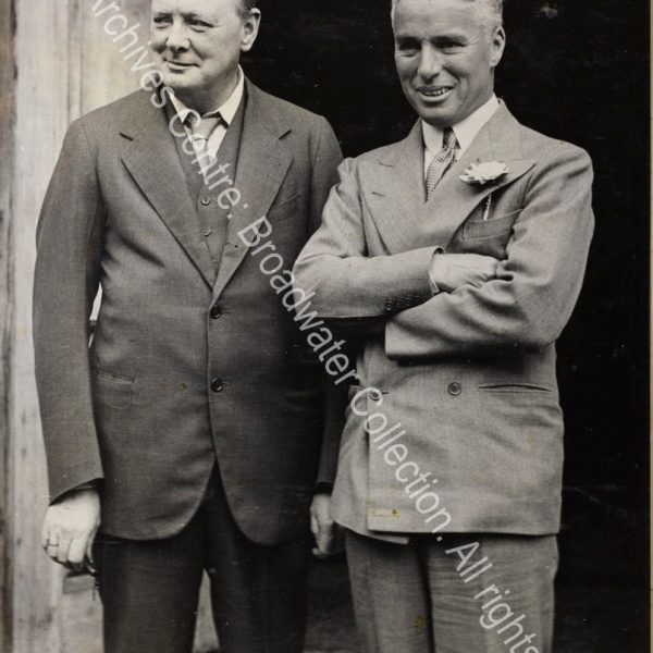 Photo shows WSC and Charlie Chaplain standing outside a doorway.