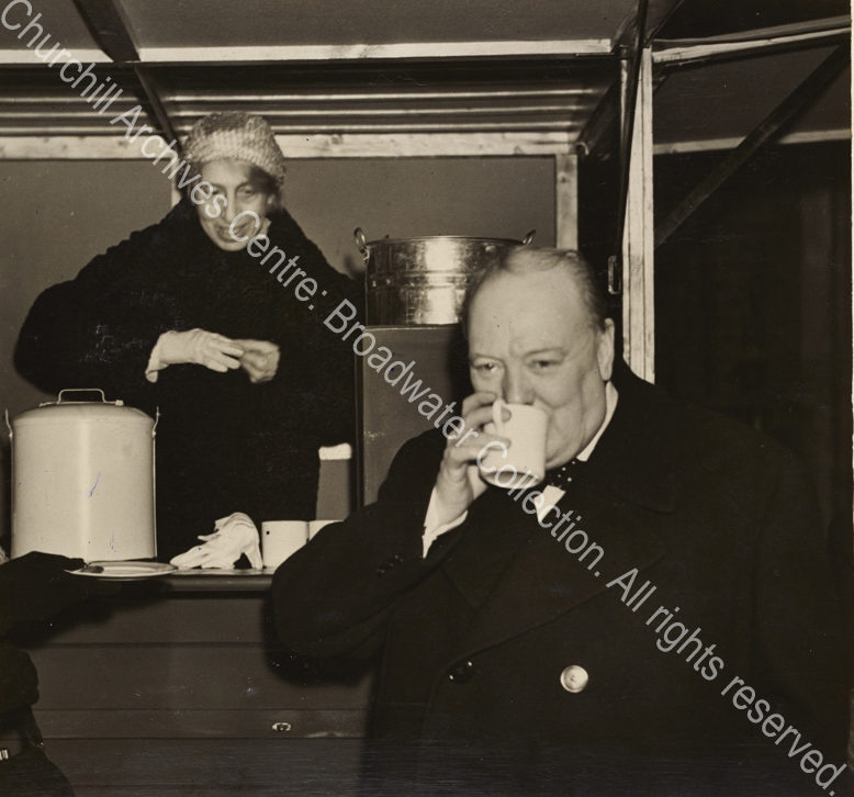 Photo shows WSC drinking from a mug. A female ?canteen worker stands behind him.