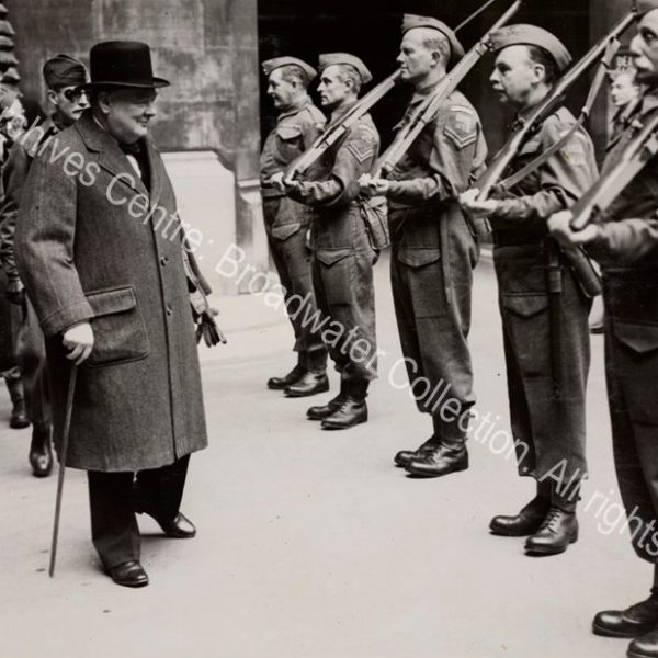 WSC inspects the Palace of Westminster Home Guard in Speaker's Court. Photo shows WSC wearing an overcoat and hat