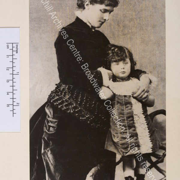 Photograph showing WSC as a toddler standing on a chair leaning against his mother. WSC has long curly hair and is wearing a velvet and lace dress