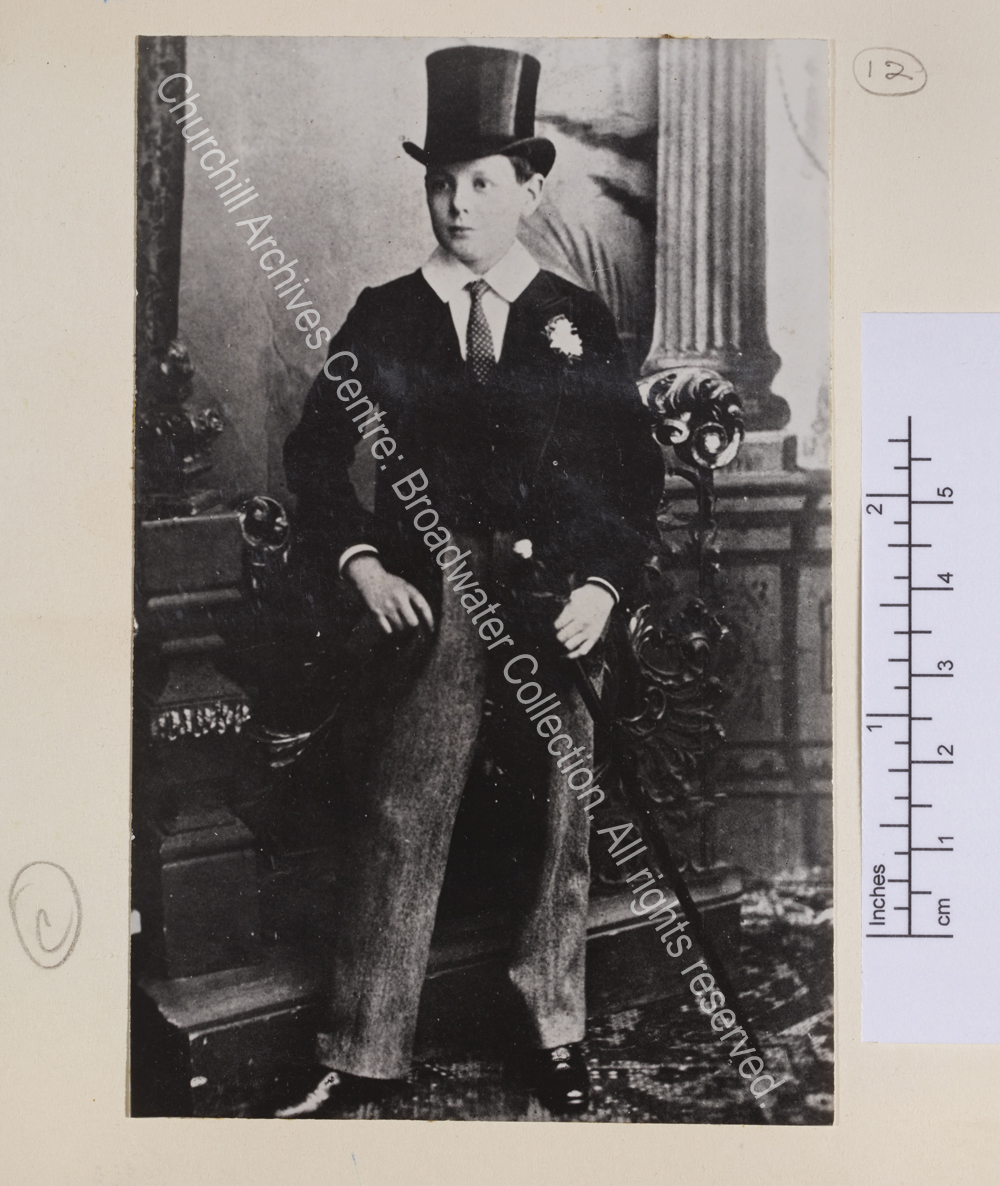 Portrait photograph of WSC as a schoolboy wearing a top hat and tailcoat and carrying a walking cane.
