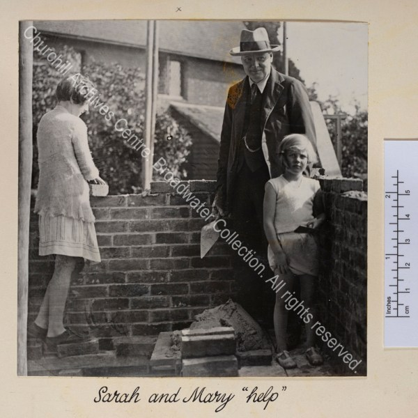 Photo of bricklaying at Chartwell. WSC stands holding a trowel with Sarah [Churchill