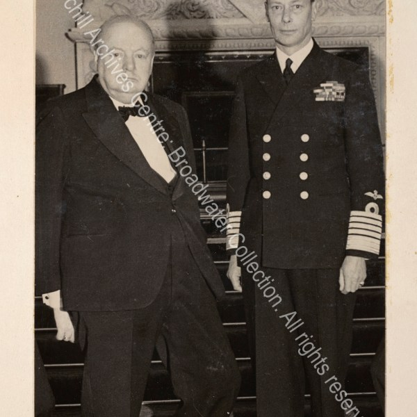 Photo shows WSC standing next to King George VI. The King is in uniform and WSC is wearing a dinner jacket and black tie.