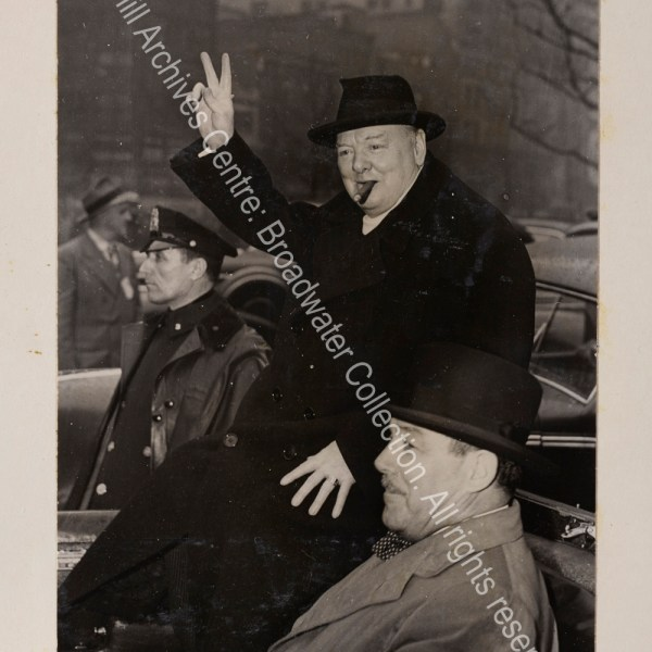Photo shows WSC in the back of an open topped car on Broadway. He is wearing an overcoat and hat and raising his hand in a victory sign. Grover Whalen sits next to him in the car.
