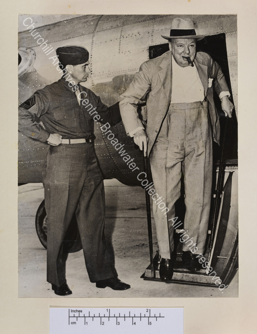 Photo shows WSC walking down the steps of a small aircraft. He is wearing a light suit and hat and has a cigar in his mouth.