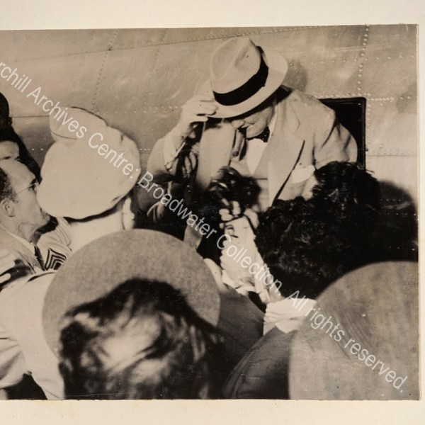 Photo shows WSC surrounded by a crowd of journalists as he disembarks from a small aircraft. He is wearing a light suit and hat and has a cigar in his mouth.