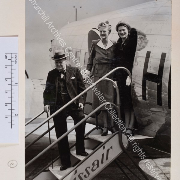 Photo shows WSC on the steps of a Swissair plane. He is wearing a pinstriped suit and waistcoat and a hat. CSC and Mary Churchill [later Lady Soames] stand together at the top of the steps smiling to the camera.