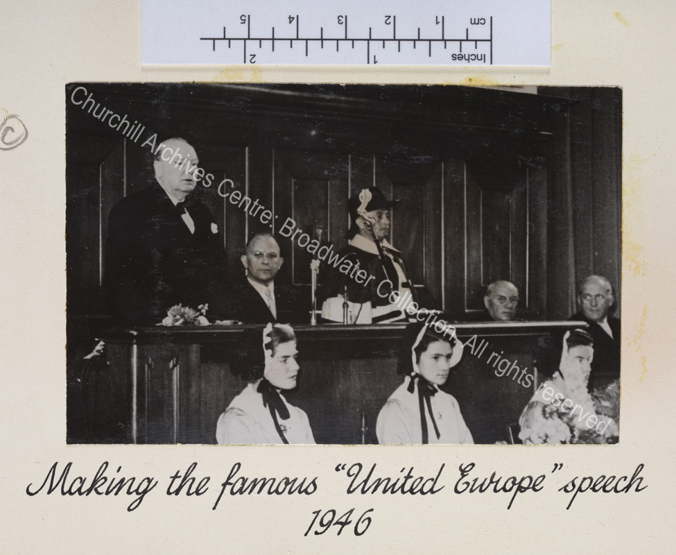 Photo shows WSC at the University of Zurich delivering his speech. Three young women wearing traditional bonnets sit in front of the lectern.