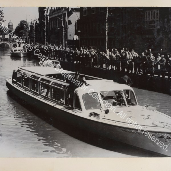 Photo shows WSC standing on board the Princess Irene wearing an overcoat and making a victory sign. Crowds of people are seen at the edge of the canal and standing on a bridge.