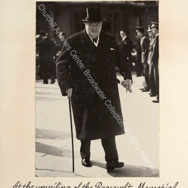 Photo shows WSC walking towards the camera. He is wearing an overcoat and top hat