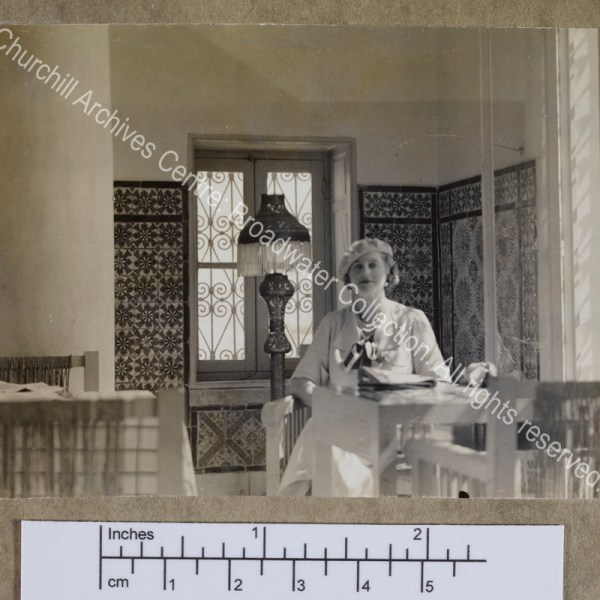 Photograph of CSC [while on a cruise of the Eastern Mediterranean on 1st Lord Moyne's yacht the Rosaura].  She is sitting at a table in a [?] cafe with tiled walls