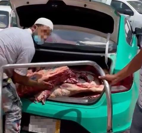 Labor loading meat into a taxi