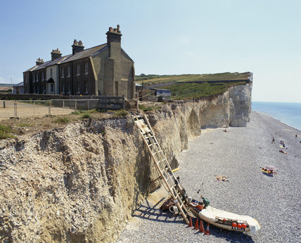 View Of House On Cliff Edge Overlooking The Pebbly Beach