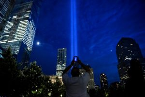 A man photographs beams of light symbolizing the two World Trade Center towers the night before the 15th anniversary of the September 11, 2001 terrorist attacks in the United States on September 10, 2016 in New York, New York. / AFP PHOTO / Brendan Smialowski