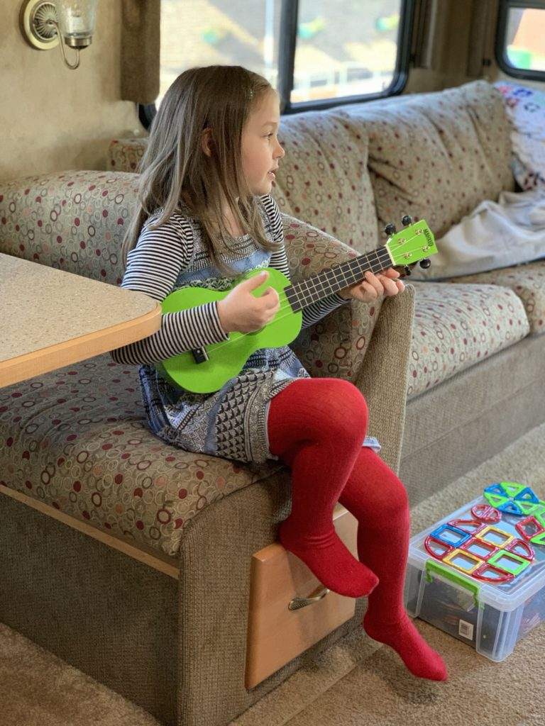 Olivia sits at the dinette playing her bright green Ukulele