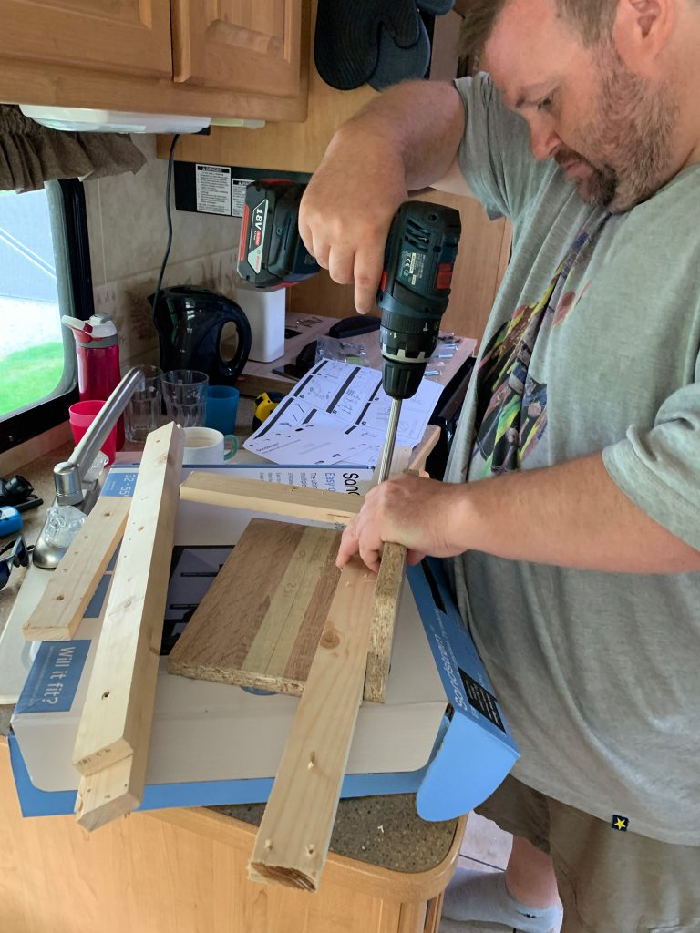 George uses a drill to assemble lengths of wood into our new TV mount