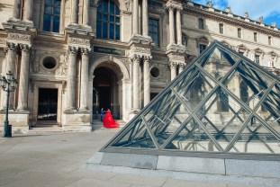 Девушка в красном платье в Лувре в Париже