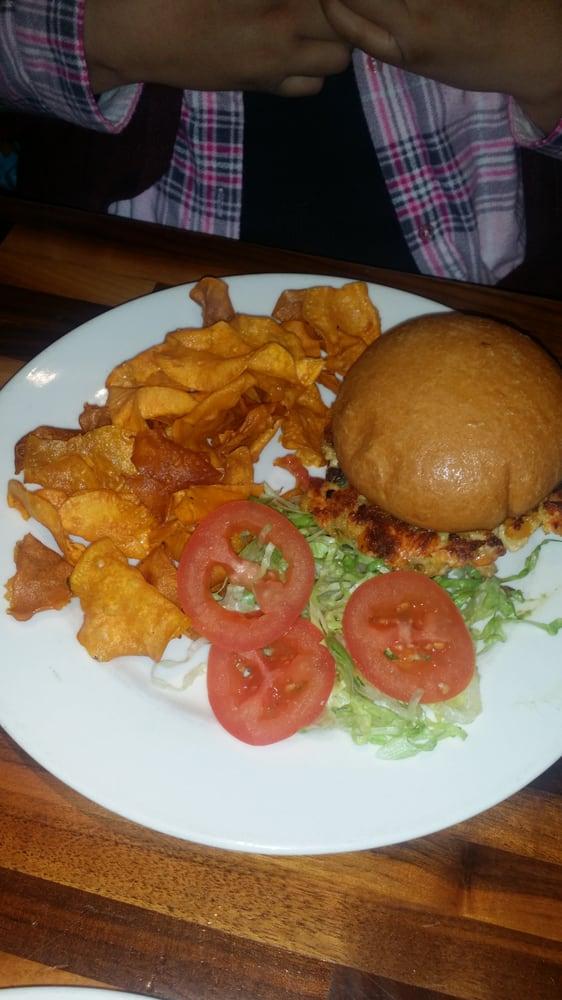 Salmon burger served with fresh sweet potatoe chips Yelp