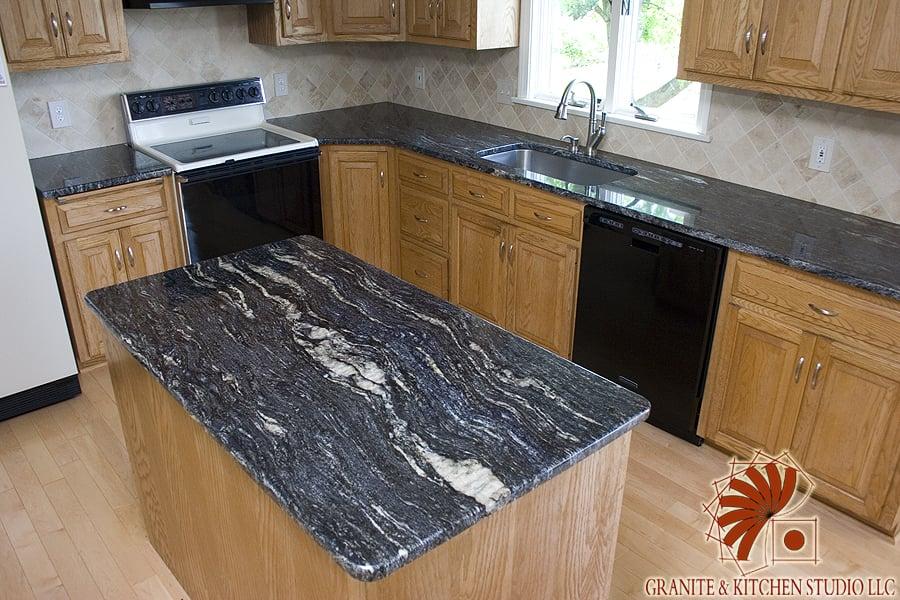 Cosmic Black Granite Countertops with a Crema Marfil Tile ... on Backsplash With Black Granite  id=84285