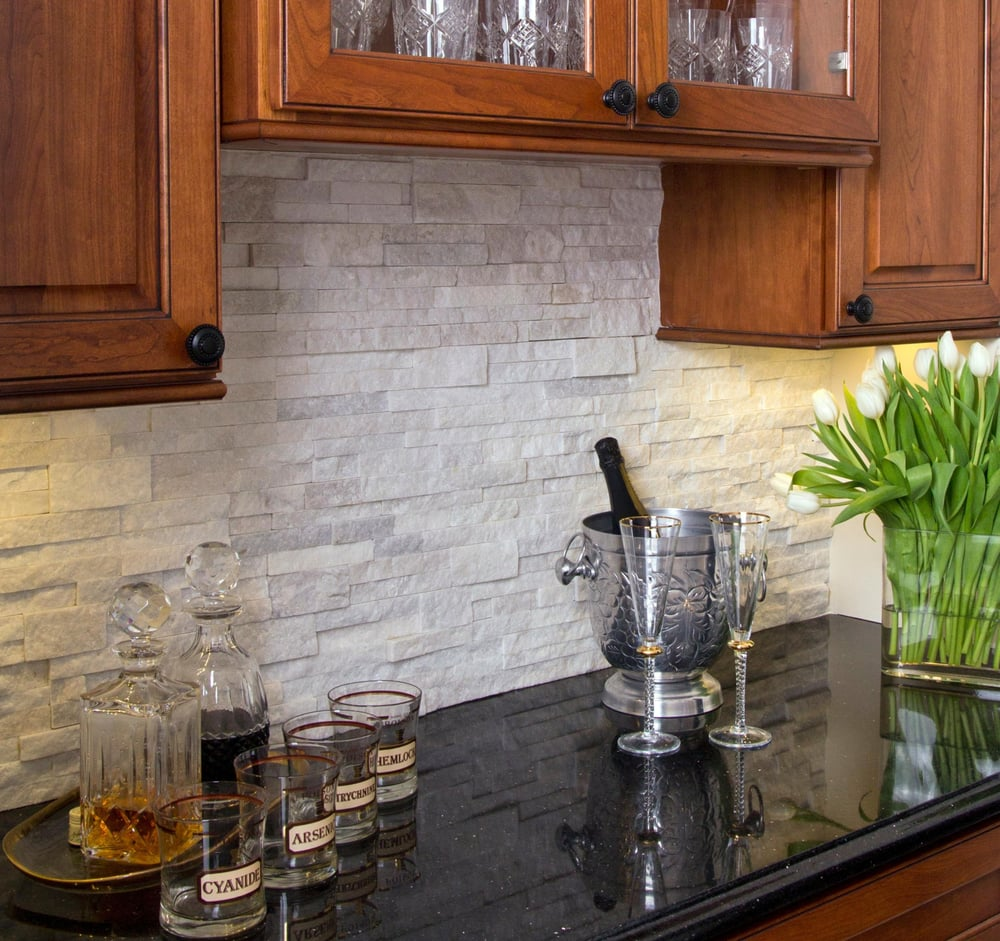 Stacked stone, quartz backsplash, under cabinet lighting ... on Backsplash Ideas For Black Granite Countertops And Cherry Cabinets  id=35787