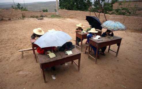 Esta foto foi tirada em 29 de Abril de 2004, às Xishan Village, a menos de 10 km de Lanzhou, capital da província de Gansu. Devido à condição estrutura perigosa de sua escola, alguns alunos têm de ter aulas ao ar livre, com um chapéu de palha e guarda-chuva para se proteger contra o sol ea chuva. (Fonte: sina.com.cn)
