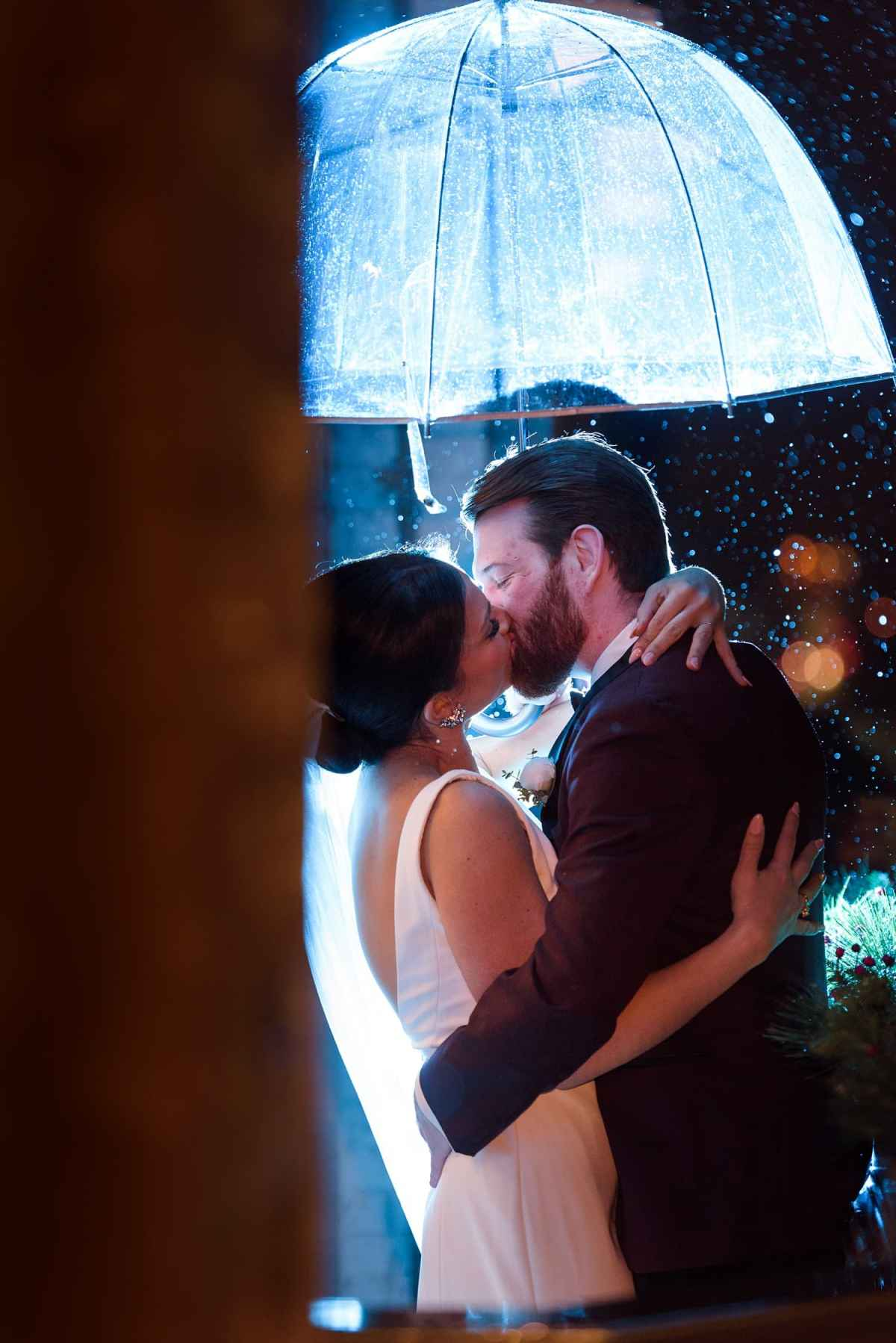 bride and groom kiss under an. umbrella in the rain at night on the tea room balcony