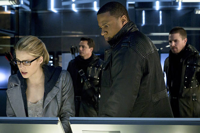 """Arrow -- """"My Name is Oliver Queen"""" -- Image AR323B_0009b -- Pictured (L-R): Emily Bett Rickards as Felicity Smoak, John Barrowman as Malcolm Merlyn, David Ramsey as John Diggle and Stephen Amell as Oliver Queen -- Photo: Liane Hentscher/The CW -- © 2015 The CW Network, LLC. All Rights Reserved."""