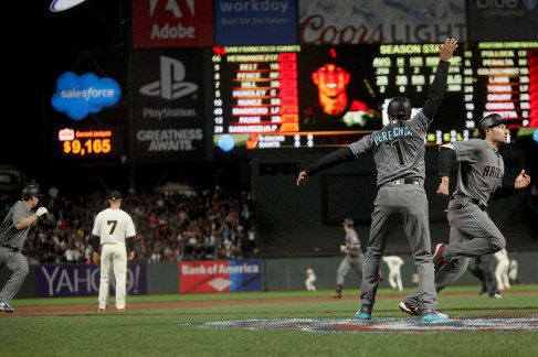 Arizona Diamondbacks third base coach Tony Perezchica (1) rounds in all the runners on base as Jake Lamb (22) connects for a three-run triple in the third inning as the Arizona Diamondbacks face the San Francisco Giants at AT&T Park in San Francisco, Calif., on Tuesday April 11, 2017.