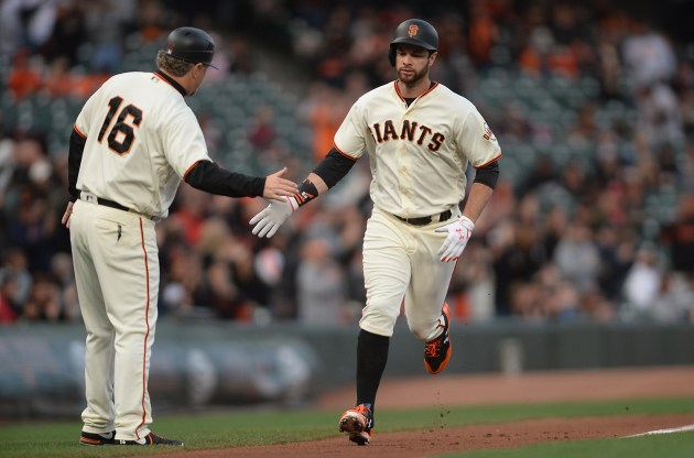 San Francisco Giants first baseman Brandon Belt (9) is congratulated by San Francisco Giants third base coach Phil Nevin (16) after a first inning home run as the Cincinnati Reds face the San Francisco Giants at AT&T Park in San Francisco, Calif., on Thursday, May 11, 2017.