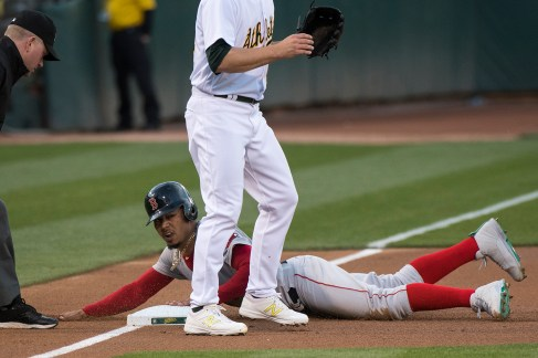 Boston Red Sox right fielder Mookie Betts (50) slides safely into third in the first inning of the game against the Oakland Athletics at the Oakland Coliseum in Oakland, Calif., on May 18, 2017.
