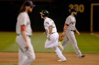 Oakland Athletics left fielder Mark Canha (20) rounds the bases after a walk off home run in the tenth inning as the Boston Red Sox face the Oakland Athletics at Oakland Coliseum in Oakland, Calif., on Friday, May 19, 2017.