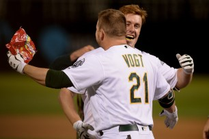 Oakland Athletics designated hitter Stephen Vogt (21) congratulates Oakland Athletics left fielder Mark Canha (20) after a walk off home run in the tenth inning as the Boston Red Sox face the Oakland Athletics at Oakland Coliseum in Oakland, Calif., on Friday, May 19, 2017.
