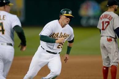 Oakland Athletics third baseman Ryon Healy (25) is waved home on a Canha triple as the Boston Red Sox face the Oakland Athletics at Oakland Coliseum in Oakland, Calif., on Friday, May 19, 2017.