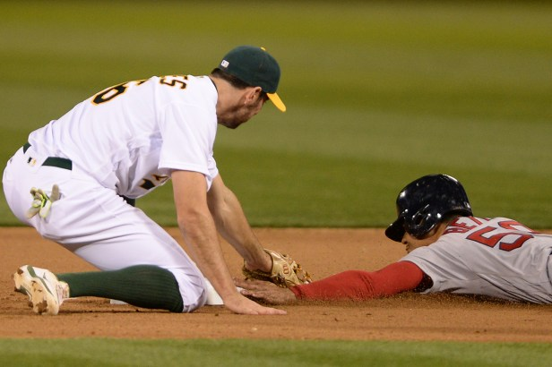 Boston Red Sox right fielder Mookie Betts (50) is tagged out by Oakland Athletics infielder Adam Rosales(16) as the Boston Red Sox face the Oakland Athletics at Oakland Coliseum in Oakland, Calif., on Friday, May 19, 2017.