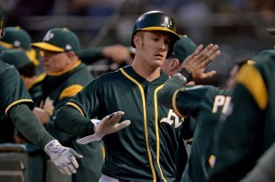 Oakland Athletics left fielder Mark Canha (20) is congratulated after scoring in the fifth inning as the Toronto Blue Jays face the Oakland Athletics at Oakland Coliseum in Oakland, Calif., on Tuesday, June 6, 2017.