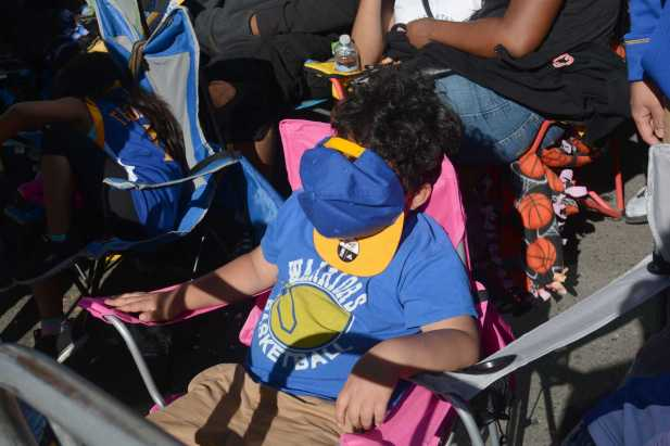 A young Warriors fan sits asleep at the Golden State Warriors championship parade in Oakland, Calif. on Thursday, Jun. 15, 2017.