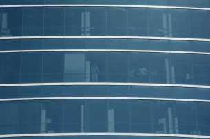Business people look out of their offices at the crowd below at the Golden State Warriors championship parade in Oakland, Calif. on Thursday, Jun. 15, 2017.