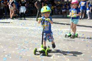 A young Warriors fan rides a scooter at the Golden State Warriors championship parade in Oakland, Calif. on Thursday, Jun. 15, 2017.