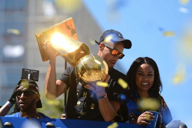 Warriors G Stephen Curry (30) holds the 2017 NBA Championship trophy as his wife Ayesha Curry smiles at the Golden State Warriors championship parade in Oakland, Calif. on Thursday, Jun. 15, 2017.