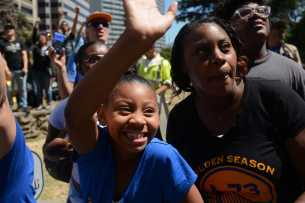 A young Warriors fan waves at the Golden State Warriors championship parade in Oakland, Calif. on Thursday, Jun. 15, 2017.