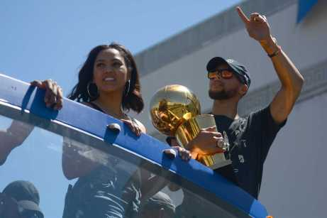 Warriors guard Stephen Curry holds the Larry O'Brien championship trophy standing next his wife Ayesha Curry at the Golden State Warriors championship parade in Oakland Thursday.