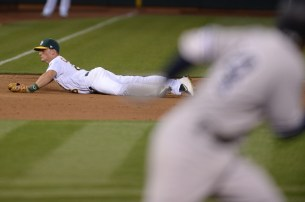 Oakland Athletics third baseman Matt Chapman (26) snags a ground ball hit by New York Yankees shortstop Ronald Torreyes (74) in the sixth inning as the New York Yankees face the Oakland Athletics at Oakland Coliseum in Oakland, Calif., on Friday, June 16, 2017.