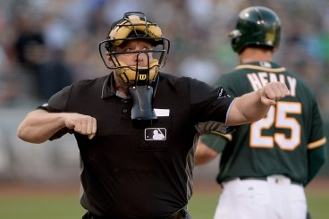 Umpire Bruce Dreckman (1) punches out Oakland Athletics third baseman Ryon Healy (25) in the second inning as the Houston Astros face the Oakland Athletics at Oakland Coliseum in Oakland, Calif., on Wednesday, June 21, 2017.