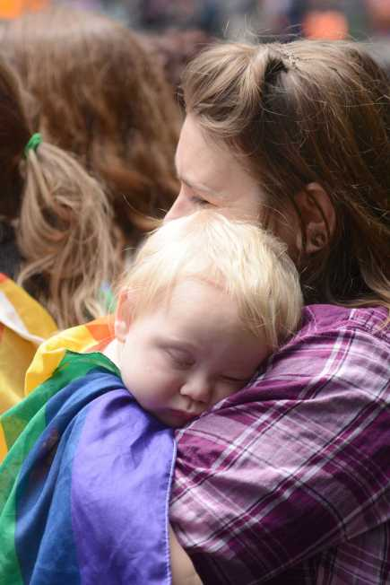 A young child rests their head on their mother's shoulder at the Pride Celebration in San Francisco, Calif., on Sunday, June 25, 2017.