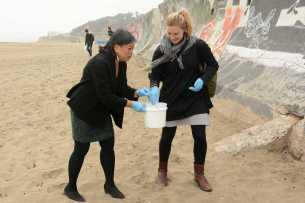 San Francisco Supervisor Sandra Lee (left) pitches in to remove cigarette butts and other litter from Ocean Beach Friday. Supervisors Katy Tang and Fewer helped launch a pilot program to encourage people to throw their cigarettes away in receptacles instead of on the streets.
