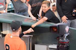 A young fan fist bumps San Francisco Giants outfielder Hunter Pence (8) before the Miami Marlins face the San Francisco Giants at AT&T Park on Friday, July 7, 2017.